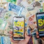 Smart phones identifying 100 Swedish krona and 50 Brazilian real; background of numerous bank notes from different countries.